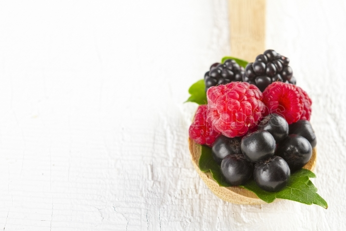 Forest fruits in wooden spoon on white wood