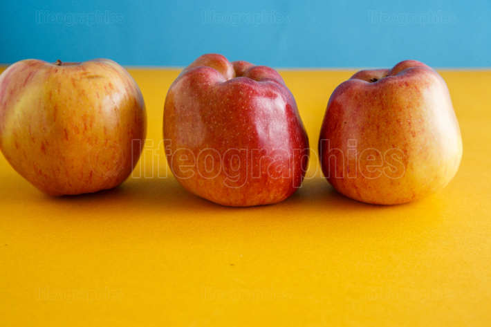 Fresh apples on yellow blue background