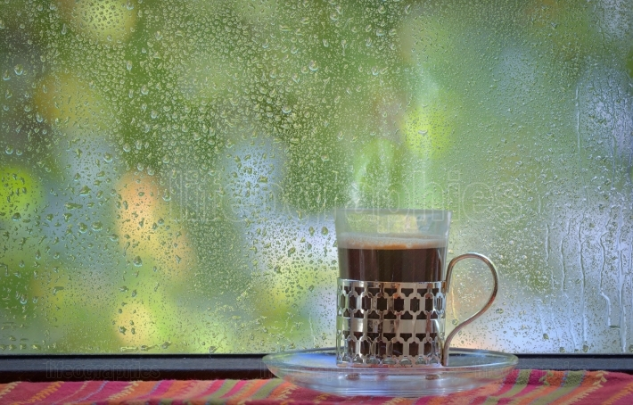 Fresh coffee cup at rainy window