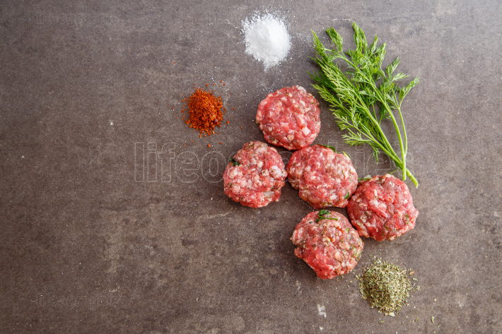 Fresh minced meat with spices and parsley on grey marble