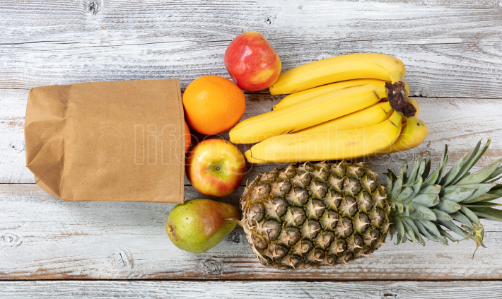 Fresh organic fruit spilling out of recyclable paper bag on whit