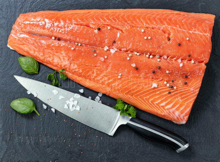 Fresh raw pacific wild king salmon on natural stone with spices