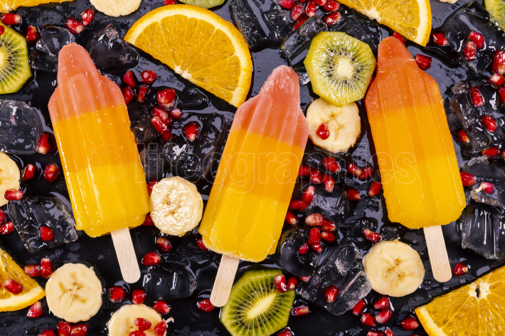 Fruit ice cream on stick with slices fruits on black slate
