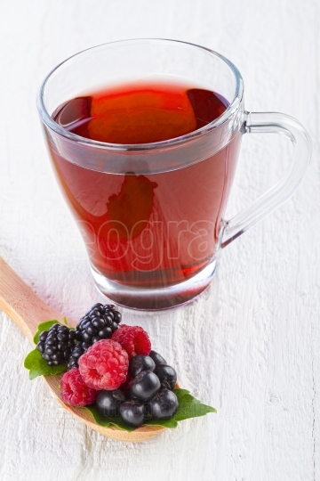 Fruit red tea with wild berries in wooden spoon on white wood