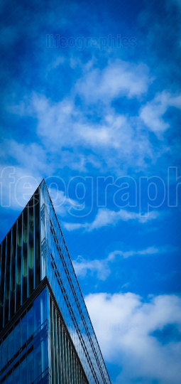 Futuristic triangular building against a clear blue sky