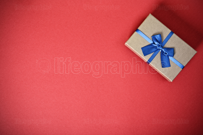 Gift box with a blue bow on red background