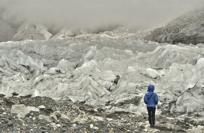 Girl climber looking at ice formations and stones layers from deep valley of Khumbu Glacier from Everest Base Camp, Himalaya.