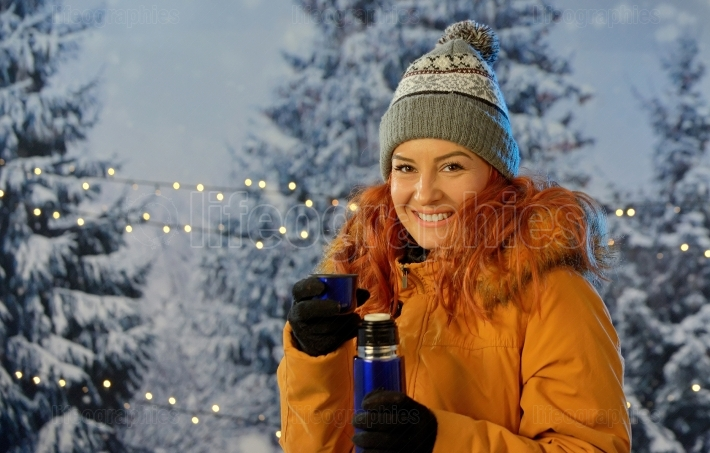 Girl drinking hot drink in winter outdoors
