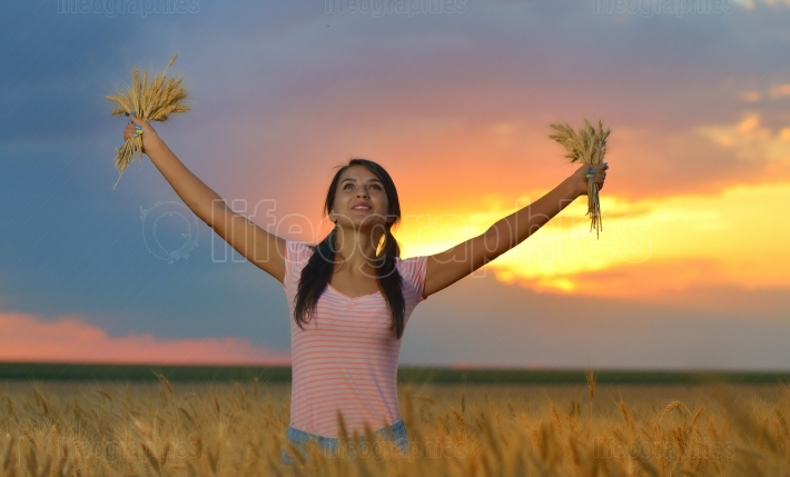 Girl feeling free in a beautiful natural setting in wheat field at sunset