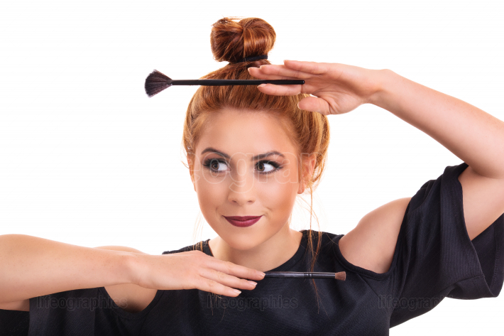 Girl framing her face with cosmetic brushes for make up
