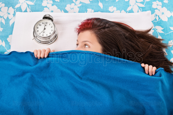 Girl hiding beneath a blanket looking at alarm clock