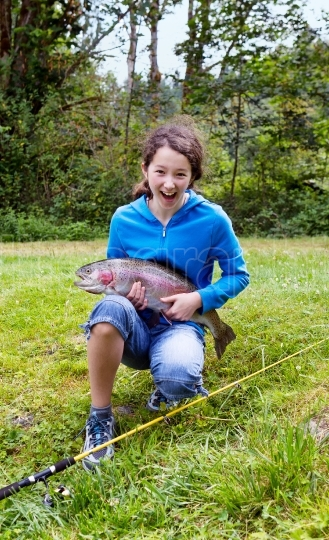 Girl holding large rainbow trout with huge smile