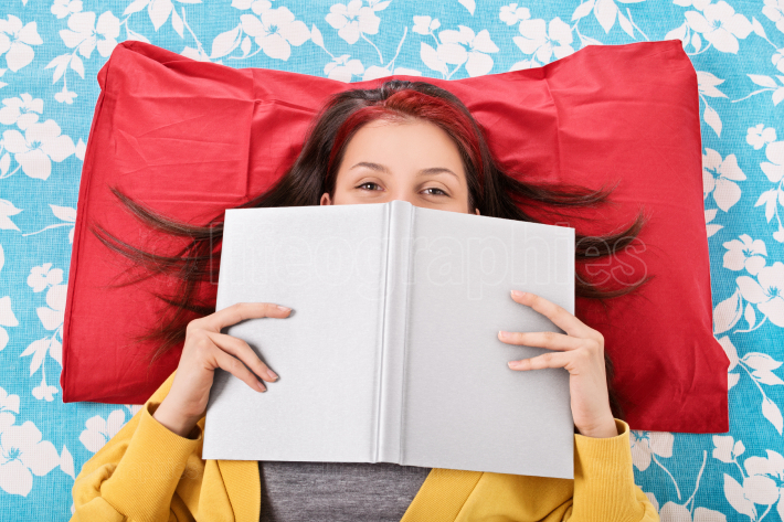 Girl in bed hiding her face behind a book