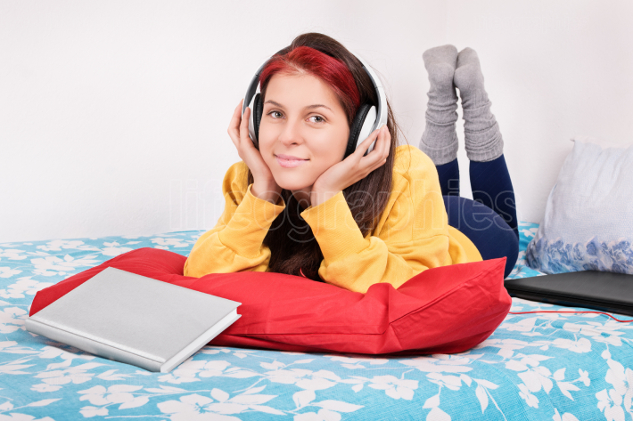 Girl in bed with headphones, book and a laptop