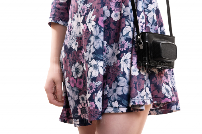Girl in flowery dress carrying vintage camera in leader bad