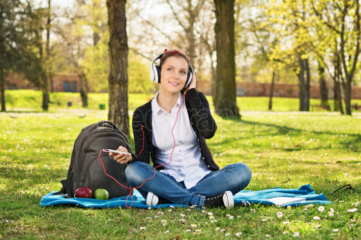 Girl student in park listening to music
