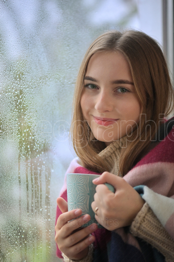 Girl With A Cup Of  Drink Stands In Front Of A Window