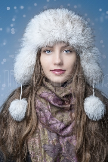 Girl with a white hat happy in the snow