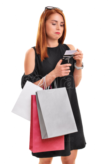 Girl with shopping bags cutting credit card with scissors