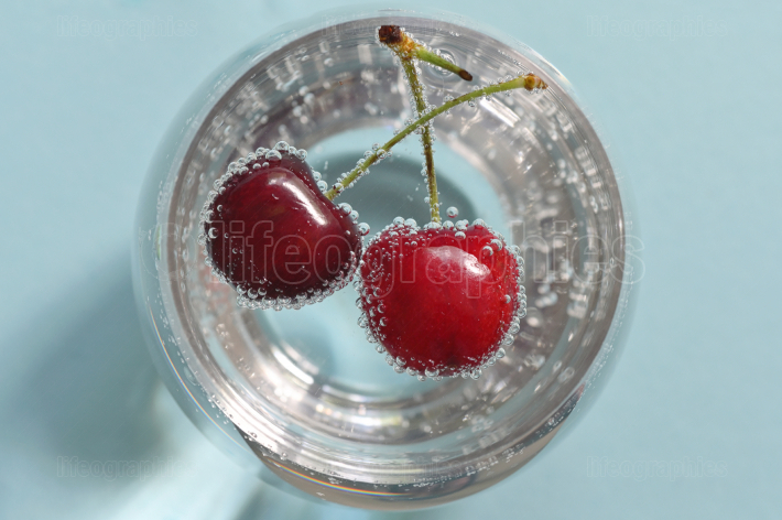 Glass of water and fresh cherries