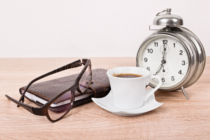 Glasses, notebook, alarm clock and coffee cup