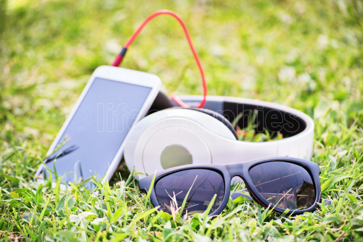 Glasses with smart phone and headphones on a meadow