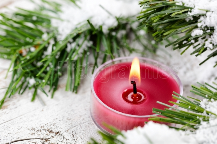 Glowing candle for Christmas holiday with evergreen and snow in
