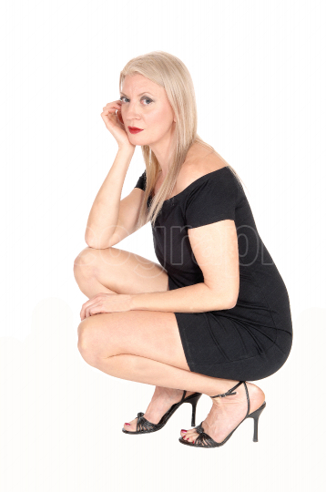 Gorgeous blond woman crouching on floor