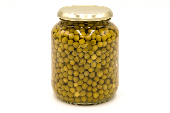 Green peas in a glass jar isolated