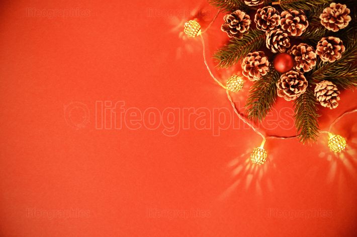 Greeting card concept with pinecones, branches and lights