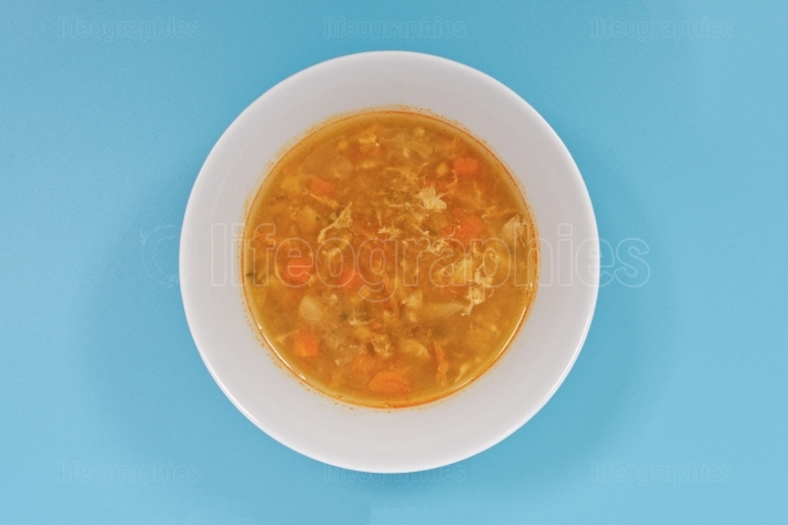 Groat soup with vegetables on a blue
