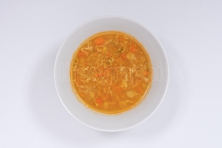 Groat soup with vegetables on a white