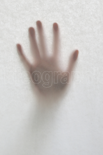 Hand Against A Blurry Glass