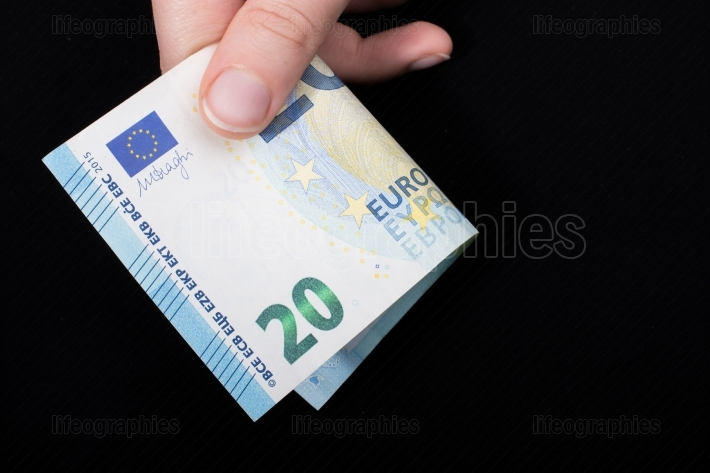 Hand holding 100 euro banknote on a black background