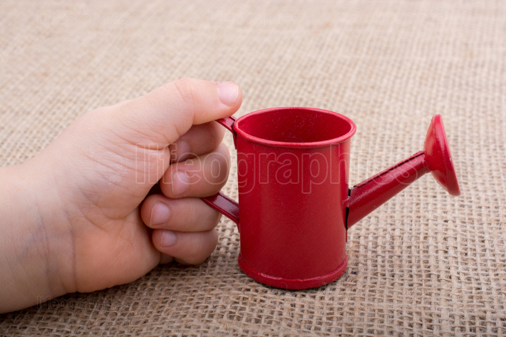 Hand holding a watering can on  canvas background