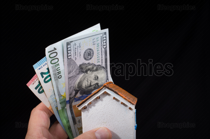 Hand holding American dollar  isolated on black background