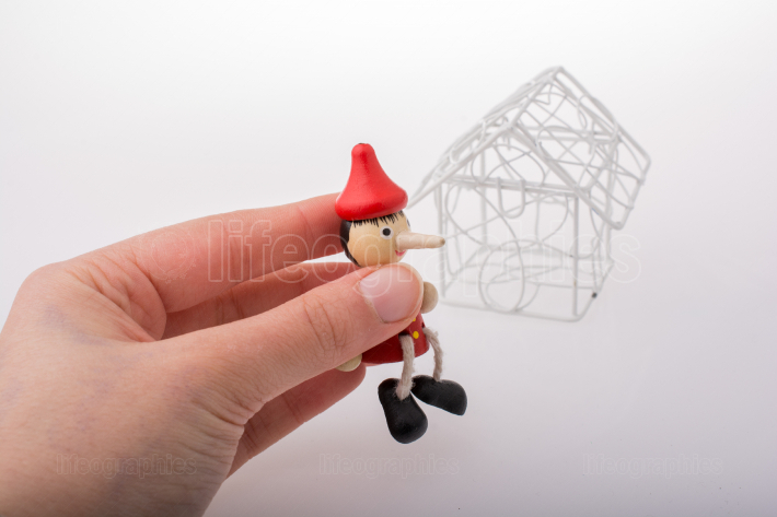 Hand holding pinocchio beside a model house