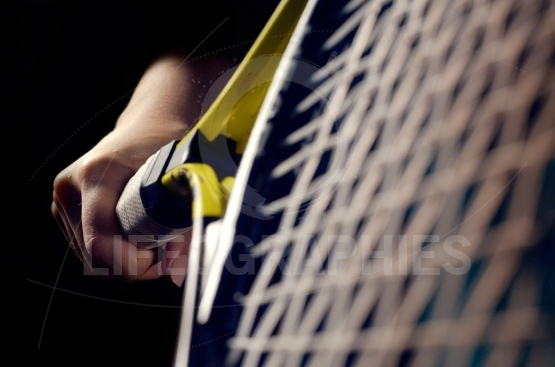 Hand on grip and swinging a tennis racket. Isolated on black bac