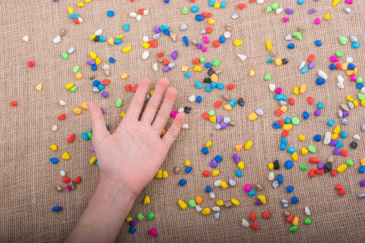 Hand placed on colorful pebbles on canvas