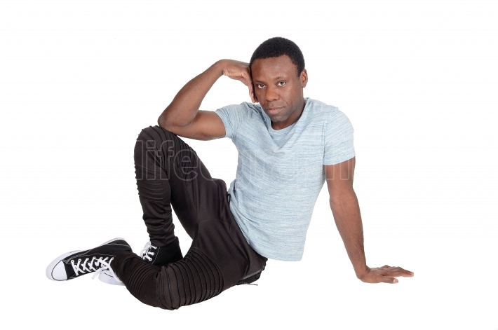 Handsome African man sitting on floor resting