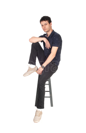 Handsome tall young man sitting on chair