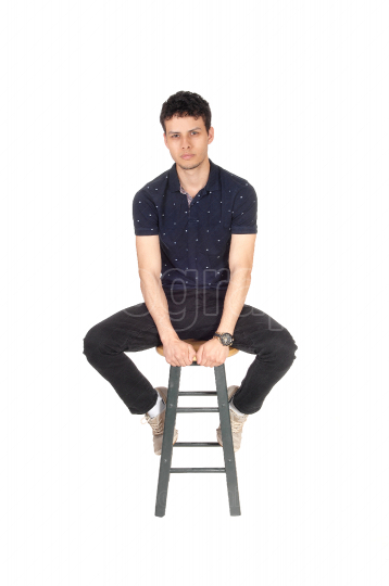 Handsome tall young man sitting on chair in the studio