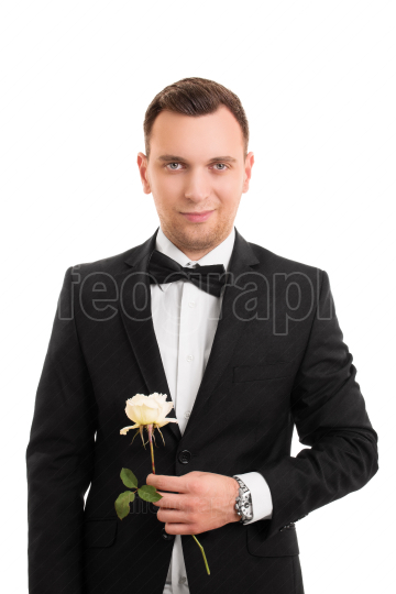 Handsome young man in a suit holding a flower