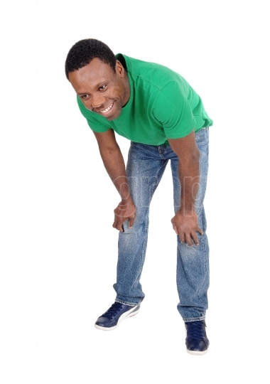 Happy African man in jeans bending down