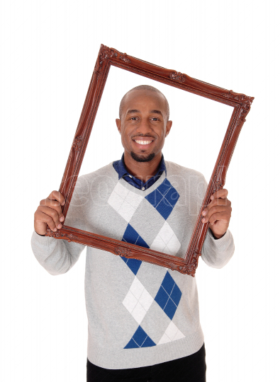 Happy African man looking touhg a picture frame