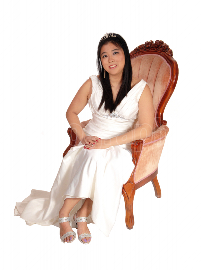 Happy bride sitting in a pink old armchair smiling