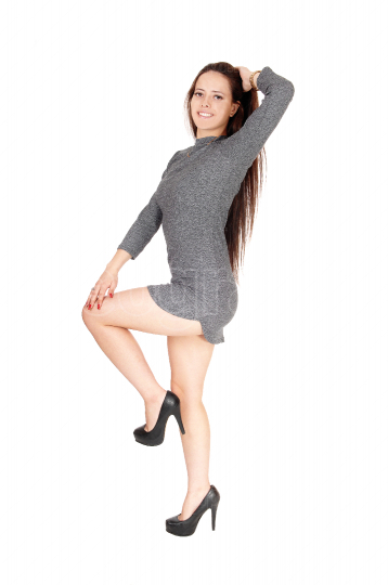 Happy dancing young woman in gray dress
