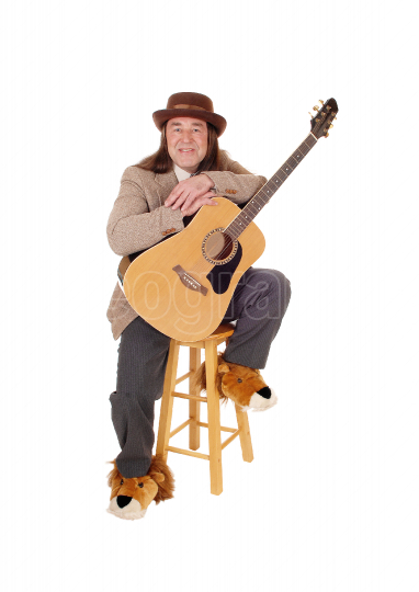 Happy musician playing guitar resting on a chair