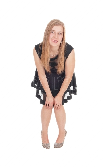 Happy woman in a short black dress bending