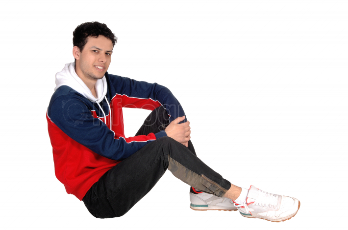 Happy young man sitting on the floor resting from exercise